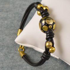 Pulsera de cuero con nudos corredizos y piezas en dorado