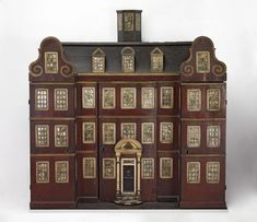 By Joy  Edmund (1712) This child's wardrobe is in the form of a house, with a hipped roof front, two Dutch-style gables, a detachable glazed hexagonal cupola, and a three-storey façade set with windows and a door. The centre front and wing fronts, all of which open, are lined with handblocked wallpaper showing stags and figures among trees.