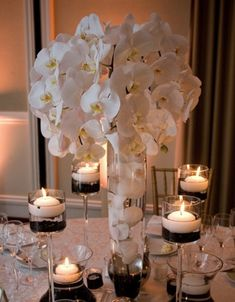 """Tall centerpieces composed of white orchids were surrounded by candleholders filled with black sand and floating candles."" I love this but maybe a different color sand for the colors Wedding Night, Gold Wedding, Wedding Reception, Wedding Flowers, Wedding Ideas, Wedding Black, Black Weddings, Wedding Shoot, Wedding Tables"