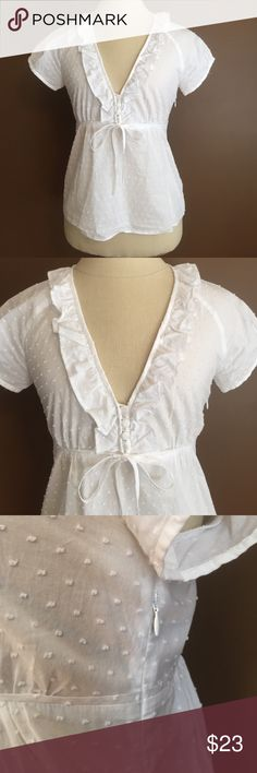 Very beautiful J Crew white cotton summer blouse!! This is a very beautiful looking and beautifully made top by J crew. It is the lightest cotton fabric with little.dot details on it , buttons down the bodice  ,and very feminine ruffles around the neckline with a bow in the front. It has a side zipper to help with putting the top on / off and also help with contouring the blouse so it can be perfectly fitted to your form. This shirt is in excellent condition and only been worn once.See…
