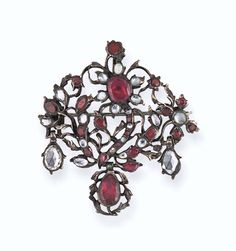 An 18th century garnet and paste pendant brooch  The scrolling foliate openwork panel set throughout with vari-shaped garnets and rose-cut pastes, suspending a central pear shaped garnet single stone in foliate border between rose-cut paste single stone drops, in silver mount with gilded reverse and foiled settings, later brooch fitting