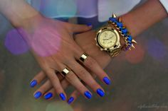 blue nail polish with gold jewelry