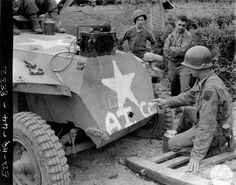 July 27, 1944. Pvt Victor Dowdle from Blackfoot, Idaho, Anti-Tank company, 18th Infantry, 1st Division on captured german half track from Panzer Lehr Division.