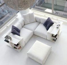 un canapé d'angle blanc avec des coussins en bleu et blanc dans le salon