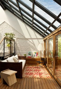 skylight and floor-to-ceiling door welcome sunshine to brighten up this balcony-to-living room