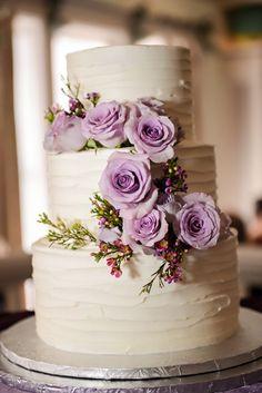 A rustic, textured three tier wedding cake with beautiful lavender roses #purpleweddingcakes