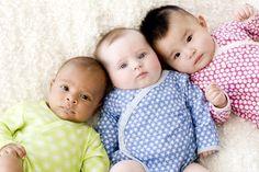 Three babies wearing colorful onesies