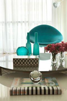 Detalhe na decoração de mesa de centro. Arranjos harmônicos e coloridos dão charme ao ambiente. Objetos em turquesa e verde tiffany dão vida ao ambiente. Projeto de design de interiores e decoração para apartamento em Moema, São Paulo.