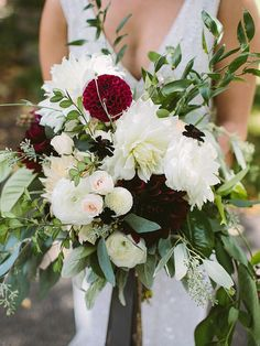 Boast dark, moody blooms against stark white florals in a chic and whimsical cascading wedding bouquet.