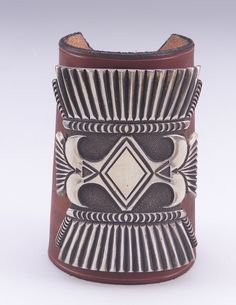 Wristguard/Ketoh by Wilson Jim (Diné/ Navajo), 1986, Silver, commercially tanned leather,  and commercial leather thong.