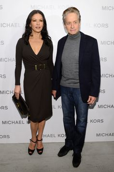 At @Michael Kors Spring 2013 runway show ///// Catherine Zeta-Jones: Chocolate stretch matte jersey v-neck wrap dress, chocolate suede peep toe Mary Jane pumps, and chocolate embossed crocodile and python Blake clutch all from the Michael Kors Fall 2012 collection.  Michael Douglas wore a Michael Kors blazer and cashmere turtleneck.