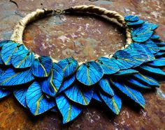 This exquisite bib necklace will be the piece of resistance of any jewelry chest. Made entirely from polymer clay, it has been sculpted, sanded, and molded entirely by hand. The necklace features an old gold color achieved with metallic waxes, but it can be customized. I currently can make it it in oxidized silver as well. The necklace body measure 5in x 1 3/4in, and the inner, unfinished circumference measure 5 1/2in. The necklace closes with a chain in a matching color that ends i...