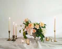 Warm toned tablescape with a cream compote, brass candlesticks, and an array of gold tinged votives