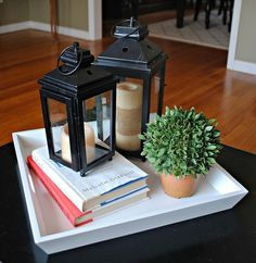 coffee table decor lanterns books and a small plant