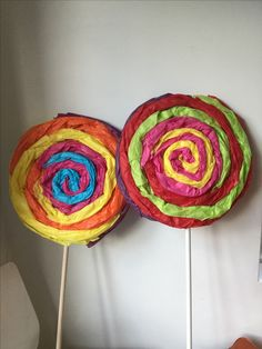 Giant wonka lollipops made from two pieces of cardboard, a stick and tissue paper.
