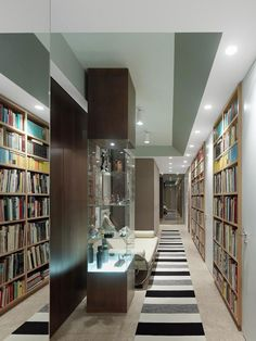 Apartment FS by Ippolito Fleitz Group Identity Architects - flush book cases and mirrored corridor end