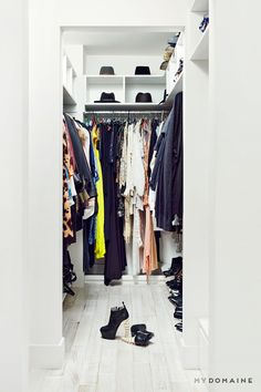 White closet fully stocked with gorgeous clothes, shoes, and hats