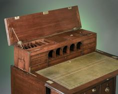 1790 ca.  Campaign Desk, English.   Mahogany mechanical desk with a leather writing surface, drawers and compartments which pop up, designed to be folded, packed and easily transported by traveling armies features bronze pulls and casters. Expansion of British Empire during 18th and 19th centuries led to production of Campaign furnishings that were stylish and practical.  via 1st Dibs 1stdibs.com  suzilove.com