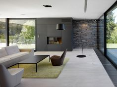 Breathtaking-Small-Open-Living-Room-Design-with-Stunning-Stone-Wall-Covering-and-Cozy-White-Sofa-and-Glossy-Black-Table-and-Charming-Arc-Flo...