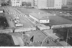 Berlin Wall 1963 - A broad view of the East Berlin checkpoint, photographed from the American OP. Cars had to zig-zag to get through - to make it harder to drive your way to freedom. - Berlin, Checkpoint Charlie, April 1963  (c) 2002 James B. Osbon