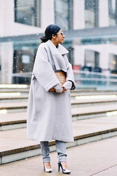 Nausheen Shah is cozy in a gray long coat, gray trousers, black and white heels, and a long-sleeve top