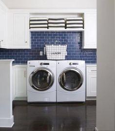 O que acha do contraste entre os azulejos azuis e os armários brancos nessa lavanderia? Linda né?