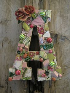 Mosaic letter A in pink and green with chippy ceramic flowers.