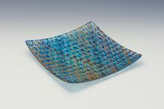 Desert Sky Plate by Richard Parrish. The Tapestry bowls, plates, and trays are both functional and beautiful. Inspired by hand woven fabrics, pieces in the Tapestry series are composed of linear patterns of glass strands creating intricate fiber like textures. Patterned sheets made with glass threads are cut, layered, and *kiln formed:kiln-forming*. Color patterns will vary slightly from piece to piece due to the process of making each piece. Food safe, hand wash. Signed on bottom.