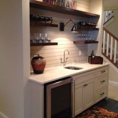 basement kitchenette with planked walls and shelves