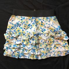 Fun floral Jessica Simpson mini Like new condition. Small Jessica Simpson floral layered mini. 100% Rayon. Layered watercolor like ruffle is shades of blue, yellow, and cream with exposed zipper back details. Elasticize waist for maximum comfort. Perfect for spring and summer. Jessica Simpson Skirts Mini