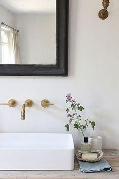 Cottage bathroom features a reclaimed wood vanity topped with a rectangular vessel sink under an aged brass faucet and a black beveled mirror.