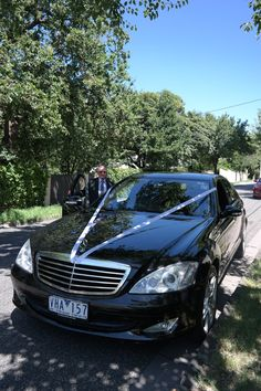 Shot of one of our professional chauffeurs near his wedding ribbon dressed Mercedes S Class, visit us on www.blackfleet.com.au or call on 1300 012 013 to discuss pricing today!