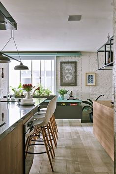 Na cozinha, a bancada de preparos se estendeaté o living, no mesmo nível que a mesa de jantar, sem limites definidos entre os dois espaços, que se integram para receber os convidados.