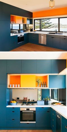 This dark blue kitchen is brightened up with white countertops and colorful pops of orange.