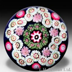 """Antique Clichy star-shaped cinquefoil garland on blue ground paperweight. A cinquefoil star-shaped millefiori garland of white/pink cog canes surrounds a green and pink concentric ring which encircles the large central pink/white cane, while five pink/white pastry mold canes nestle in the inner folds of the garland and five pink/white cog canes punctuate the outer loops, on translucent deep cobalt blue over white ground. Diameter 2 9/16"""". $ 4,500"""