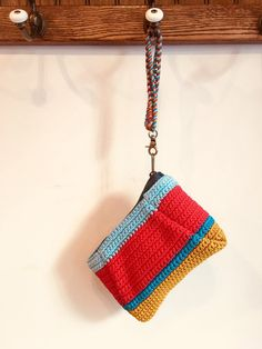 """Elliot Mann's Flags Pouch is entirely hand made. Featuring a crocheted body with a covered chain wrist hands and zipper closure. A colorful """"go to"""" that lifts your spirit. Width x Length Flags, Straw Bag, Pouch, Zipper, Chain, Handmade, Spirit, Hands, Closure"""