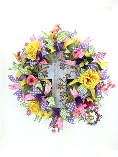 Deco Mesh Easter door wreath with He Has Risen Cross in lavender, yellow and pink by www.southerncharmwreaths.com.