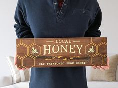 Honey sign made from real, reclaimed mahogany wood. Painted with cream and gold metallic paint. Sign measures 18 long by 6 high. Hanging hardware comes already attached. Item is sealed with a clear coating to keep sign protected and easy to clean. Each of our designs is hand crafted