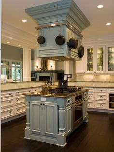 In this transitional kitchen, a pale blue island houses the oven, gas cooktop and mounted range hood. Equipped with a pot rack, pot filler and extra cabinets, the full-service island is the culinary hub of this bright white kitchen.