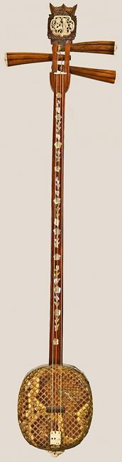 Sanxian, China, ca. 1850. Long-necked lute. Three strings. Resonator covered with python skin. Carved ivory tailpiece. Peghead plaque depicts garden scene. Hand-carved bat effigies on peghead and endpiece. Many cultures in Southeast Asia regard the bat as a harbinger of good luck. Floral, mother-of-pearl inlay on neck and resonator. The sanxian's use in accompanying narrative song and as a low voice in ensemble playing has guaranteed its role in Chinese music tradition.