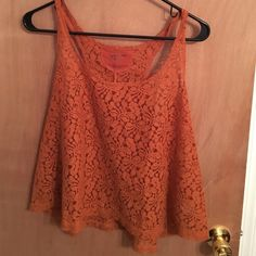 Burnt orange high- low tank top Stunning color! Burn orange lace see through top. Awesome with a bandeau underneath or bralette. Perfect condition. Fits true to size. Arizona Jean Company Tops Tank Tops