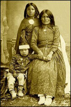 Portrait de femme Chiricahua, Neschila (La femme qui cligne de l'œil), Mère de Natches, et ses deux enfants. Photographié 1881. Archives nationales anthropologiques, de la Smithsonian Institution.