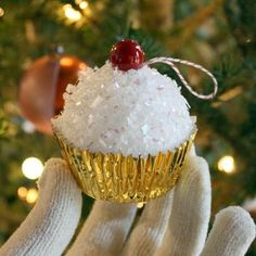 cupcake ornament: Styrofoam ball, Elmer's glue, white confetti snow, metallic cupcake wrappers, hot glue, plastic berry and a colorful string make up these fun cupcake ornaments.