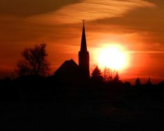 The sun sets the sky on fire behind St. John the Baptist Catholic Church, rural Belle Plaine, Minnesota.  Photography by Audrey Kletscher Helbling