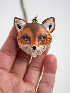 This one of a kind, or ooak fox pendant was sculpted with polymer clay, painted in acrylics, and sealed with a protective matte varnish. It hangs