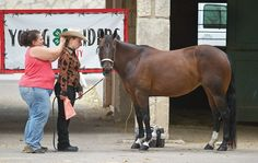 Nikki McKinney (left) from Boone, fixes her daughter, Taylor, 10, hair before she and her horse QT takes center stage for the Showmanship competition during the Pueblo County Fair horse show. (Chieftain photo by John Jaques, July 7, 2012)
