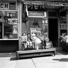 Four kids sitting on a bench in front of a neighborhood store with one little girl bending over in front of them. Undated, New York, NY