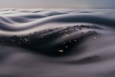 """Italian photographer Lorenzo Montezemolo climbed Mt. Tamalpais to capture Marin County, California covered with a river of fog lit by a full moon. He later wrote that he had """"compressed 186 seconds of moonlit fog into an instant."""""""
