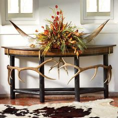 """Consider this the perfect marriage between the stately and elegant lines of the classic demilune sofa table and the untamed spirit that speaks to your soul. Handcrafted right here in Texas, this table embodies the strenuous life with magnificent elk antlers and rough-hewn reclaimed oak and spruce timber finished to full luster. Please allow 10-12 weeks for delivery. 72""""W x 33""""H. Made in USA. Note: Due to differences in dye lots, climate, the uniqueness of the artisan's applicatio..."""