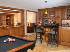 Basement bar remodel featuring granite countertops, custom cabinetry, and a game table.  Perfect for family entertaining!